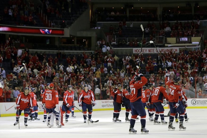 The Washington Capitals salute the fans after their win over the Toronto Maple Leafs in an NHL hockey game Tuesday, April 16, 2013 in Washington. The Capitals won 5-1. (AP Photo/Alex Brandon)