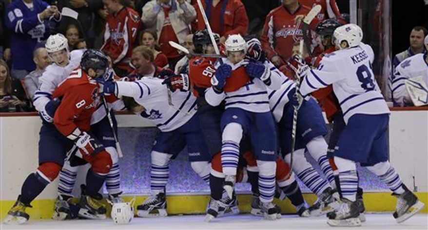 Toronto Maple Leafs defenseman Jake Gardiner (51), left, and Washington Capitals left wing Alex Ovechkin (8), from Russia, and others, scuffle after center Nicklas Backstrom, from Sweden, was hit by center Jay McClement in the first period of an NHL hockey game Tuesday, April 16, 2013 in Washington. (AP Photo/Alex Brandon)