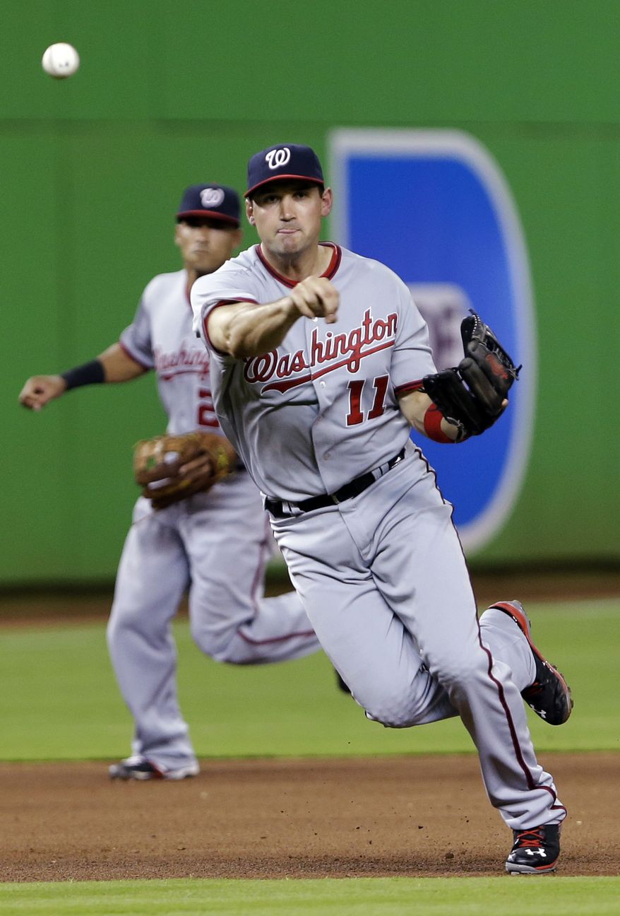 Washington Nationals third baseman Ryan Zimmerman (11) commits a throwing error as he tries to put out Miami Marlins' Placido Polanco at first base during the fourth inning of a baseball game, Tuesday, April 16, 2013, in Miami. Behind Zimmerman is shortstop Ian Desmond. The Marlins won 8-2. (AP Photo/Wilfredo Lee)