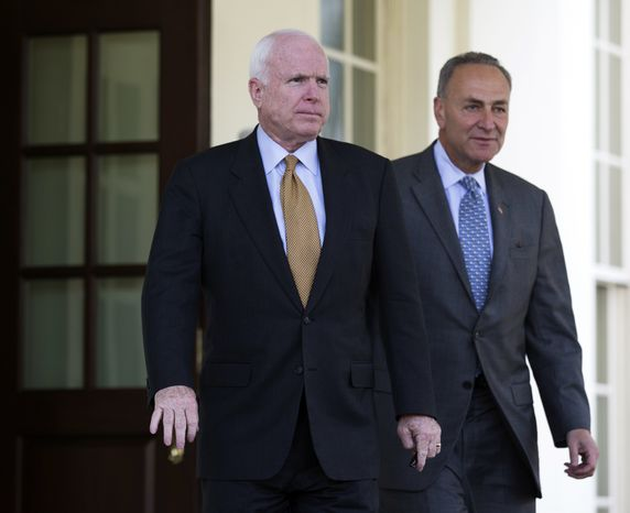 **FILE** Sens. John McCain (left), Arizona Republican, and Charles Schumer, New York Democrat, walk from the West Wing of the White House to talk to the media in Washington on April 16, 2013, following a meeting with President Obama on immigration. (Associated Press)