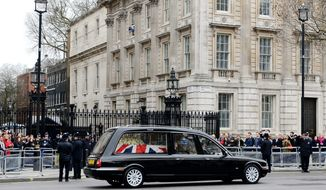 A hearse transporting the coffin containing the body of former British Prime Minister Margaret Thatcher makes its way past Downing Street in London, England, Wednesday, April 17, 2013. (AP Photo/Gareth Cattermole, Pool)