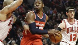 Washington Wizards guard John Wall (2) looks to pass against Chicago Bulls forward Carlos Boozer, left, and guard Kirk Hinrich during the first half of an NBA basketball game in Chicago, Wednesday, April 17, 2013. (AP Photo/Nam Y. Huh)