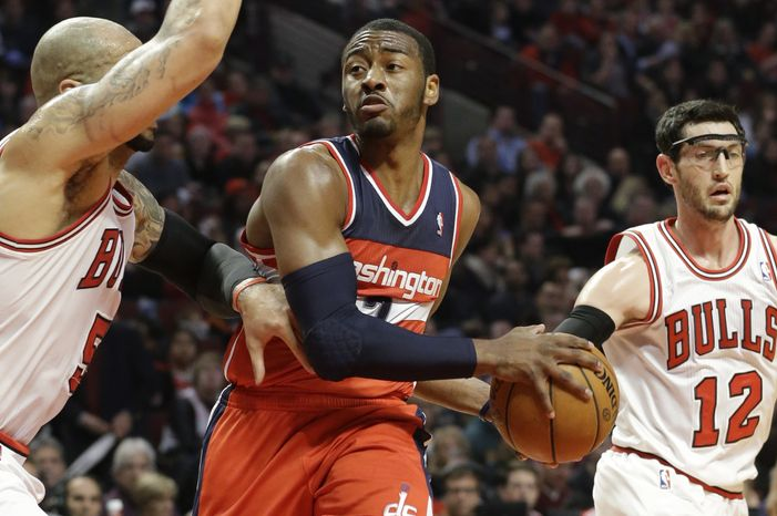 Washington Wizards guard John Wall (2) looks to pass against Chicago Bulls forward Carlos Boozer, left, and guard Kirk Hinrich during the first half of