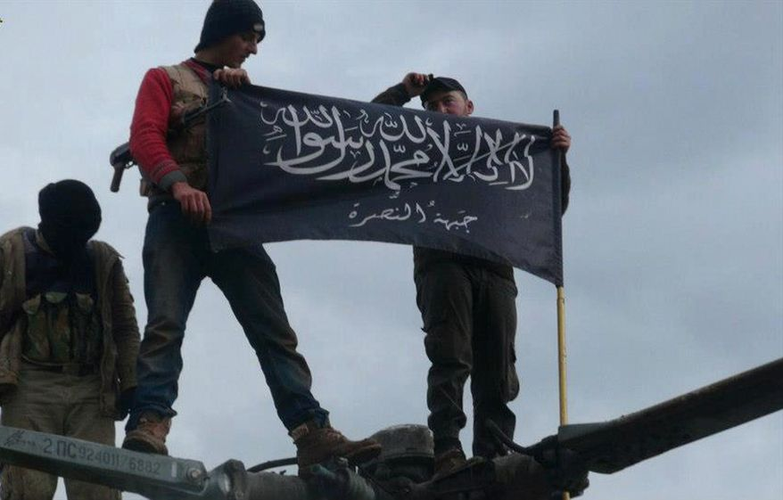** FILE ** Rebels from al-Qaeda-affiliated Jabhat al-Nusra wave their brigade flag as they step atop a Syrian air force helicopter at the Taftanaz Air Base, which was was captured by the rebels, on Friday, Jan. 11, 2013, in Idlib province in northern Syria. (AP Photo/Edlib News Network)