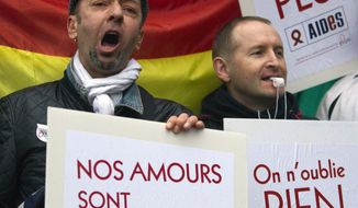 """** FILE ** People demonstrate for equal rights with placards and flags in Paris, France, Wednesday, April 10, 2013. A gay rights watchdog group says that the number of reported homophobic acts has risen in France in recent weeks, amid nationwide protests over a bill under parliamentary debate that would legalize gay marriage. Placards reads, """"Our love is stronger, and 'We forget nothing.' """" (AP Photo/Jacques Brinon)"""