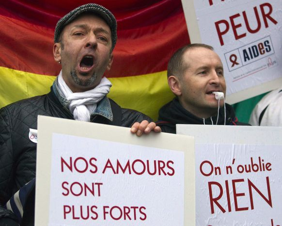 "** FILE ** People demonstrate for equal rights with placards and flags in Paris, France, Wednesday, April 10, 2013. A gay rights watchdog group says that the number of reported homophobic acts has risen in France in recent weeks, amid nationwide protests over a bill under parliamentary debate that would legalize gay marriage. Placards reads, ""Our love is stronger, and 'We forget nothing.' "" (AP Photo/Jacques Brinon)"