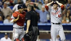 Washington Nationals catcher Kurt Suzuki, left, argues with home plate umpire Greg Gibson that he tagged Miami Marlins' Chris Valaika, not shown, at home during the fifth inning of a baseball game in Miami, Wednesday, April 17, 2013. Nationals pitcher Ross Detwiler reacts at right. (AP Photo/J Pat Carter)