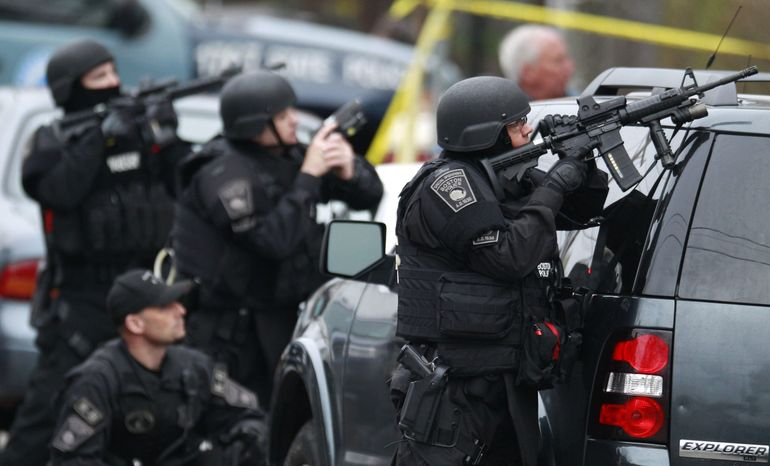 Police in tactical gear surround an apartment building while looking for a suspect in the Boston Marathon bombings in Watertown, Mass., Friday, April 19, 2013. All residents of Boston were ordered to stay in their homes Friday morning as the search for the surviving suspect in the marathon bombings continued after a long night of violence that left another suspect dead. (AP Photo/Charles Krupa)