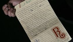Handwritten lyrics and notes by Brian Wilson from his notebook are displayed in London on April 18, 2013. A large collection of the Beach Boys' early compositions, contracts, publishing agreements, handwritten songs and musical manuscripts will be auctioned this month in one lot. (Associated Press)
