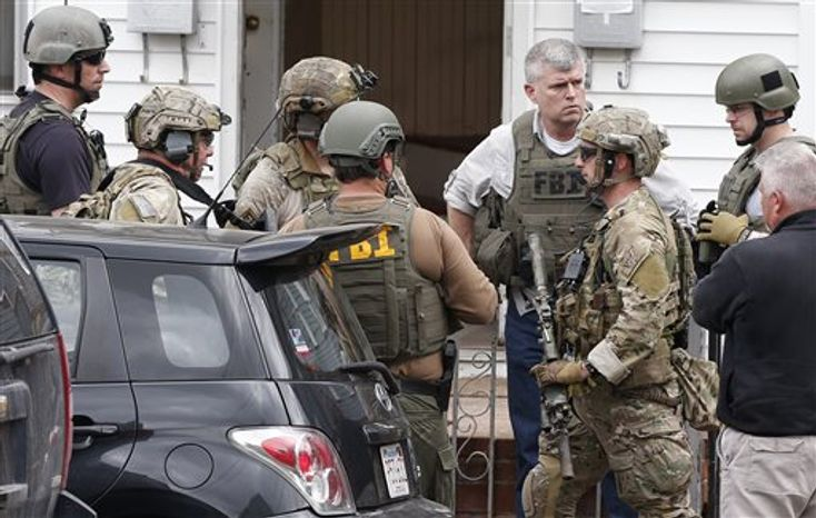 Heavily armed FBI agents gather next door to 410 Norfolk Street in Cambridge, Mass., Friday, April 19, 2013. Two suspects in the Boston Marathon bombing killed an MIT police officer, injured a transit officer in a firefight and threw explosive devices at police during a getaway attempt in a long night o