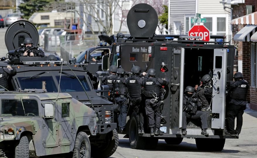 Tactical teams drive through a neighborhood while searching for a suspect in the Boston Marathon bombings in Watertown, Mass., Friday, April 19, 2013.  Two suspects in the Boston Marathon bombing killed an MIT police officer, injured a transit officer in a firefight and threw explosive devices at police during a getaway attempt in a long night of violence that left one of them dead and another still at large Friday, authorities said as the manhunt intensified for a young man described as a dangerous terrorist.  (AP Photo/Charles Krupa)