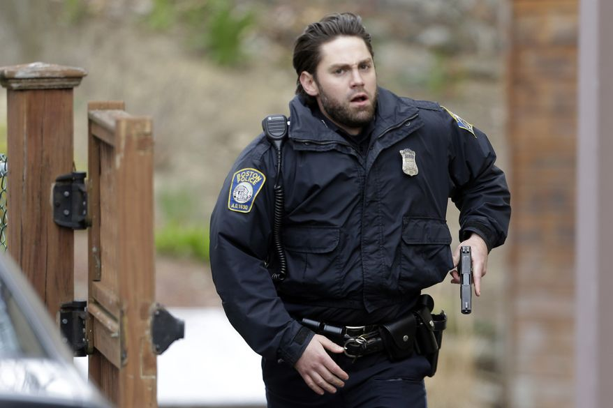 A police officer runs with his weapon drawn as he conduct a search for a suspect in the Boston Marathon bombings, Friday, April 19, 2013, in Watertown, Mass.  Two suspects in the Boston Marathon bombing killed an MIT police officer, injured a transit officer in a firefight and threw explosive devices at police during a getaway attempt in a long night of violence that left one of them dead and another still at large Friday, authorities said as the manhunt intensified for a young man described as a dangerous terrorist. (AP Photo/Matt Rourke)
