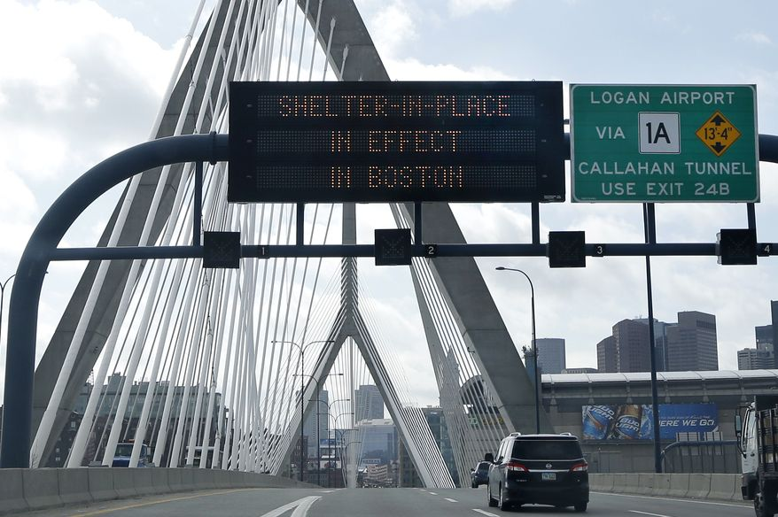 """A message calling for citizens of Boston to """"Shelter in Place"""" flashes on a sign on I-93 near the Zakim Bridge in Boston Friday, April 18, 2013. The Boston area was all but paralyzed as a manhunt continued for Dzhokhar Tsarnaev, one of the two suspects in the Boston Marathon bombing who authorities say killed an MIT police officer and hurled explosives at police in a car chase and gun battle overnight that left his brother, Tamerian Tsarnaev, dead. (AP Photo/Elise Amendola)"""