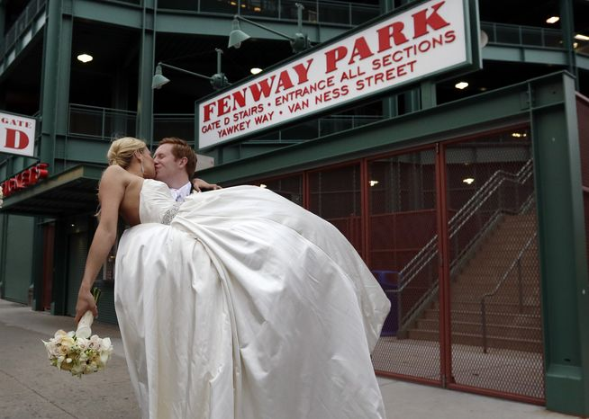 Bridal couple Sarah and Neil Sands, of Dublin, Ireland kiss as they pose for pictures outside an empty Fenway Park in Boston Friday, April 19, 2013. The Boston Red Sox baseball game against the Kansas City Royals was postponed because of the city-wide lockdown due to the police manhunt for a young man described as a dangerous terrorist who is a suspect in Monday's Boston Marathon bombings. (AP Photo/Elise Amendola)