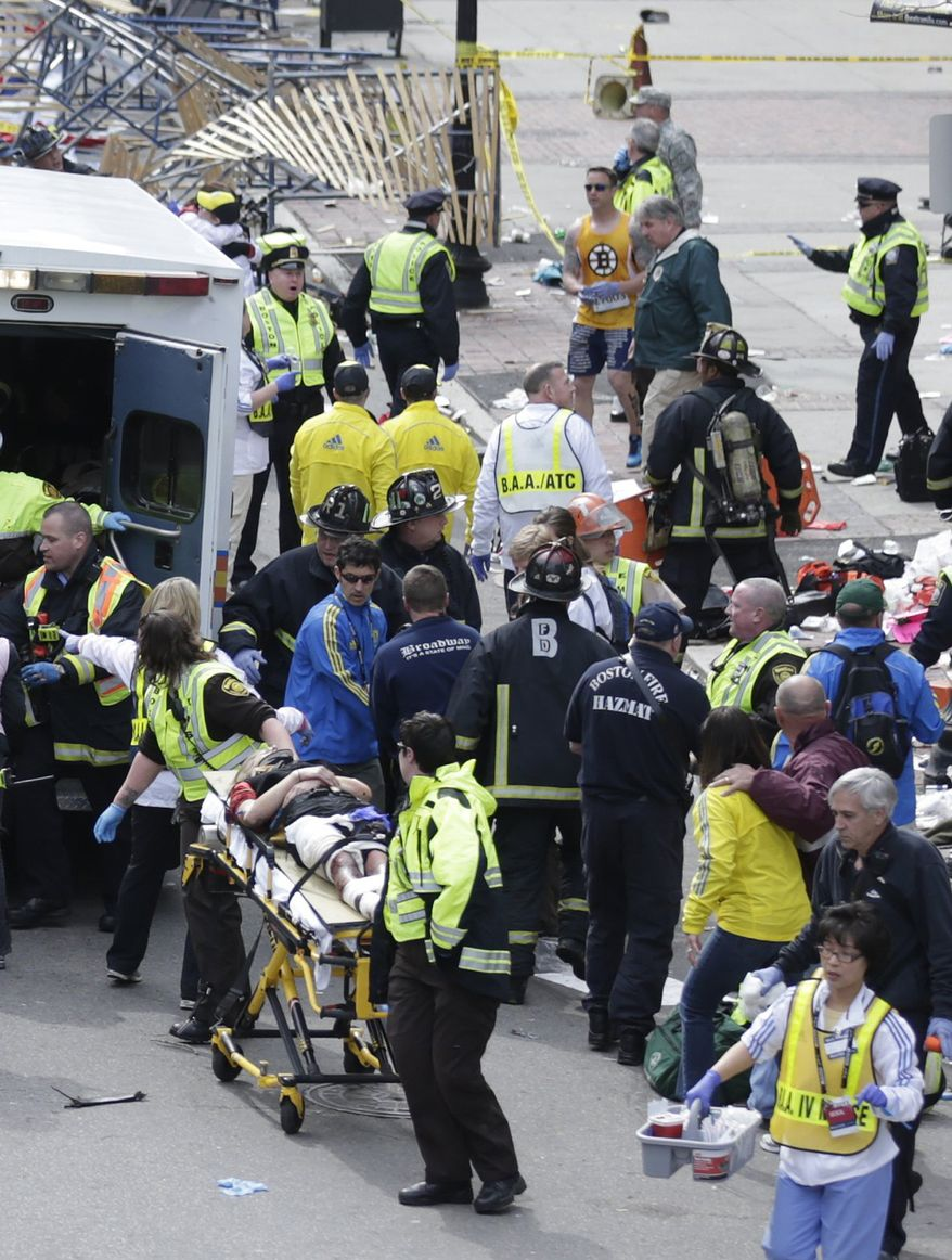 FILE - In this Monday, April 15, 2013 file photo, medical workers aid injured people at the finish line of the 2013 Boston Marathon following an explosion in Boston. Runner Lucas Carr can be seen in the upper center of the photo in the yellow Boston Bruins shirt. Carr, an Army Sergeant who served in the middle east, assisted several of the injured by applying tourniquets. (AP Photo/Charles Krupa, File)