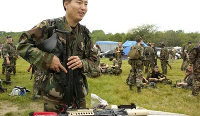 ** FILE ** Michael Kim of Columbia, Md., prepares for his first airsoft game. Many participants have military experience or are in law enforcement and play to keep their skills sharp. (The Washington Times)