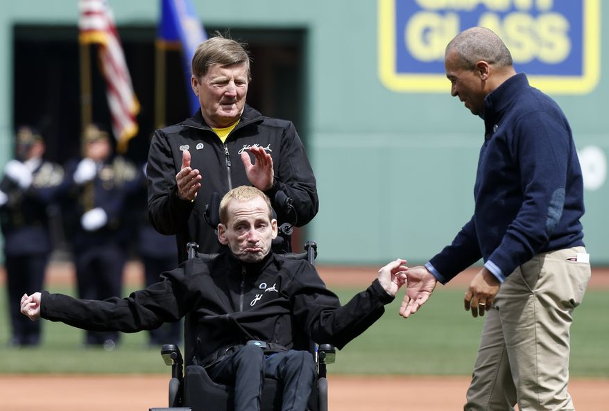 Massachusetts Gov. Deval Patrick (right) greets marathoners Rick Hoyt (below) and his father, Dick, before the ceremonial first pitch in a baseball game between the Boston Red Sox and the Kansas City Royals in Boston on Saturday, April 20, 2013. (AP Photo/Michael Dwyer)