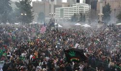 Attendees numbering in the tens of thousands smoke marijuana simultaneously at 4:20 p.m. at the Denver 420 pro-marijuana rally at Civic Center Park in Denver on Saturday, April 20, 2013. (AP Photo/Brennan Linsley)