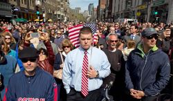 A moment of silence in honor of the victims of the Boston Marathon bombing is observed at 2:50 p.m. Monday on Boylston Street near the race finish line, exactly one week after the tragedy. (Associated Press)