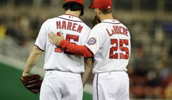Washington Nationals starting pitcher Dan Haren (15) and first baseman Adam LaRoche (25) talk on the mound during a baseball game against the St. Louis Cardinals at Nationals Park Monday, April 22, 2013, in Washington. (AP Photo/Alex Brandon)