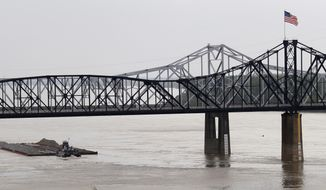 ** FILE ** A river motor vessel and its barges pass underneath the Mississippi River Bridge in Vicksburg, Miss., on Tuesday, April 16, 2013. River flow navigation is back to stages above last year's extreme low-water period along the Mississippi-Louisiana borders. (AP Photo/Rogelio V. Solis)