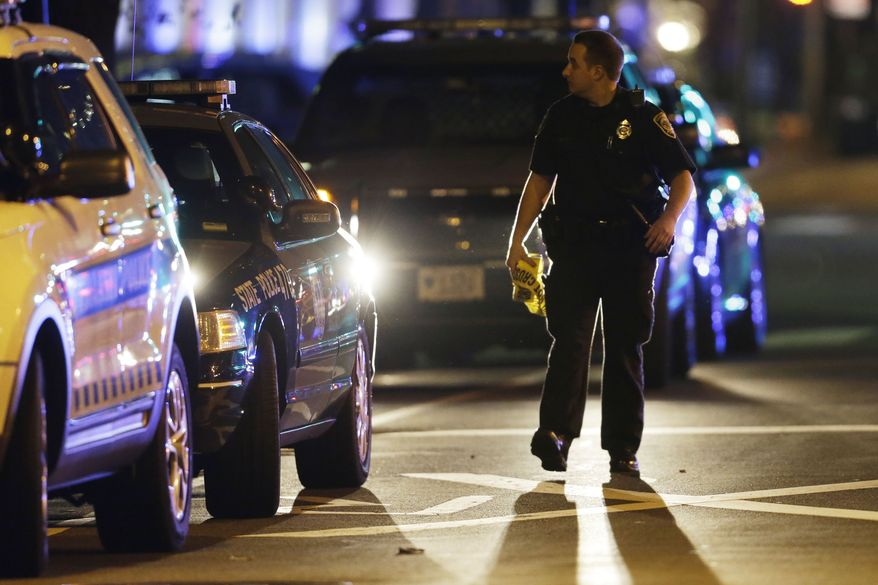 A police officer secures an area near the Massachusetts Institute of Technology campus on Friday, April 19, 2013, in Cambridge, Mass., after an MIT police officer was fatally shot. (AP Photo/Matt Rourke)