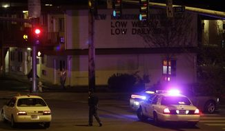 A Washington State Patrol trooper directs a driver away from a street blocked off several blocks from the scene of an overnight shooting that police said left five people dead, Monday, April 22, 2013, at an apartment complex in Federal Way, Wash. (AP Photo/Ted S. Warren)