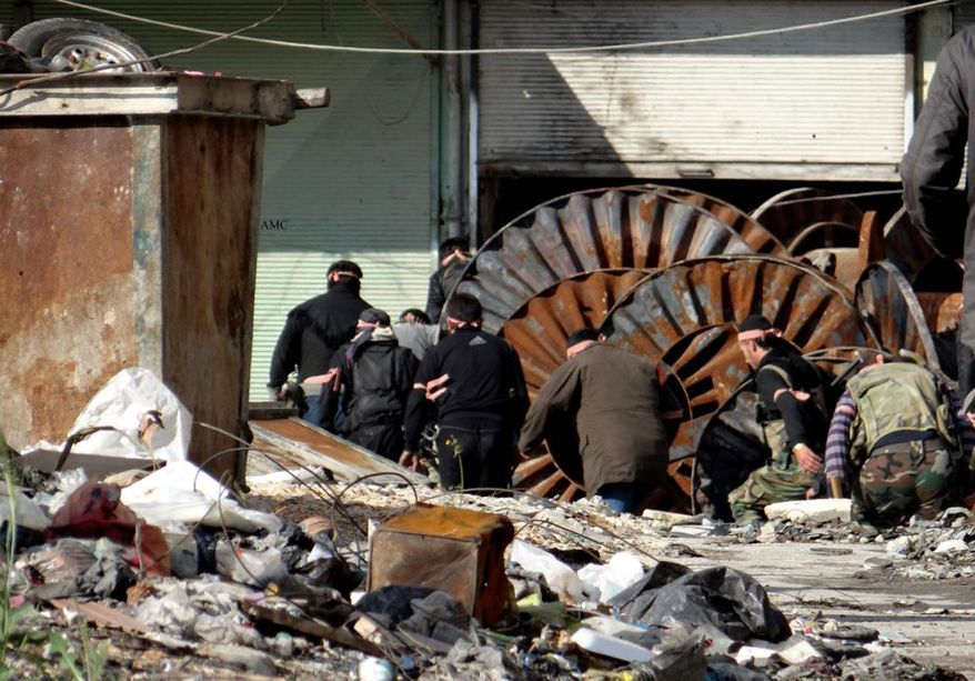 This citizen journalism image provided by Aleppo Media Center AMC which has been authenticated based on its contents and other AP reporting, shows members of the free Syrian Army hiding behind scrap metal during an attack against Syrian government forces, in the neighborhood of al-Amerieh in Aleppo, Syria, Sunday, April. 21, 2013. (AP Photo/Aleppo Media Center AMC)