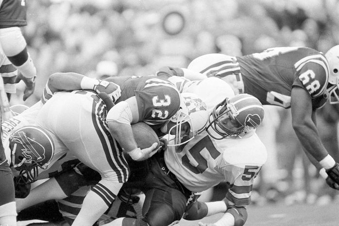 New England Patriots Craig James, left, crashes into Buffalo Bills Jim Haslett, right, for a gain during the first quarter NFL action at Sullivan Stadium in Foxboro, Mass., Nov. 11, 1984. (AP Photo/Elise Amendola)