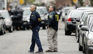 ** FILE ** FBI agents walk along Norfolk Street in Cambridge, Mass., on April 19, 2013. (Associated Press)