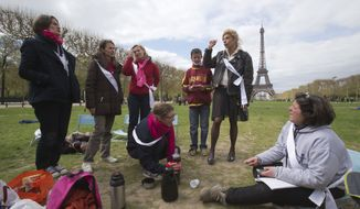 The comedian Frigide Barjot (second from right), leader of the movement against gay marriage, talks to the media as she visits mothers taking part in a vigil to protest French President Francois Hollande's social reform on same-sex marriage and adoption, in front of the Eiffel Tower in Paris on Monday, April 22, 2013. (AP Photo/Michel Euler)