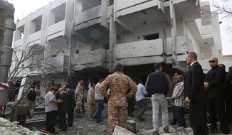 Security officers and officials inspect the site of a car bomb that targeted the French Embassy wounding two French guards and causing extensive material damage in Tripoli, Libya, Tuesday, April 23, 2013. (AP Photo/Abdul Majeed Forjani)