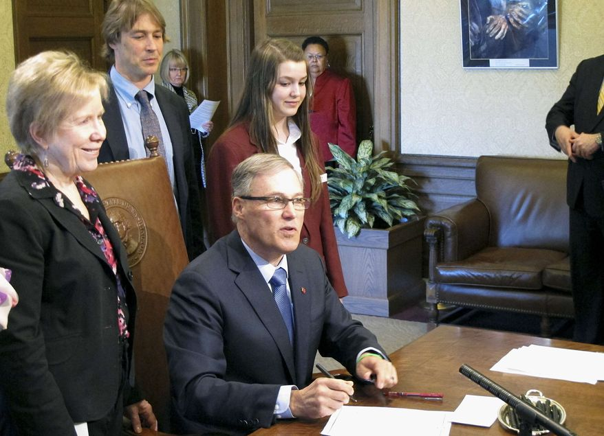 Gov. Jay Inslee, seated, signs a measure to make state statutes gender-neutral, joined by bill sponsor Sen. Jeannie Kohl-Welles, left, on Monday, April 22, 2013, in Olympia, Wash. The measure is the final installment of a multiyear project to replace thousands of references to male-centric words in state law with gender-neutral terms. (AP Photo/Rachel La Corte)