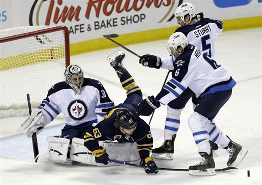 Buffalo Sabres' Tyler Ennis (63) battles for the puck with Winnipeg Jets' Ron Hainsey (6) and Mark Stuart (5) in front of goalie Ondrej Pavelec, of Czech Republic, during the second period of an NHL hockey game in Buffalo, N.Y., Monday, April 22, 2013. (AP Photo/David Duprey)