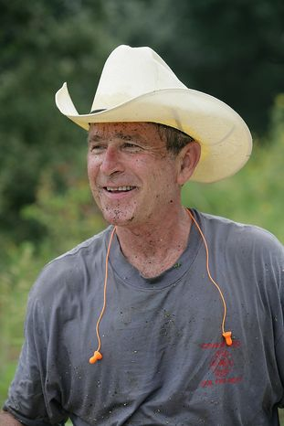 President George W. Bush bears witness to brush clearing as he takes a break from trail work during August vacation at Prairie Chapel Ranch in Crawford, Texas.   Photographs by Eric Draper from Front Row Seat: A Photographic Portrait of the Presidency of George W. Bush(Copyright © 2013). For more information visit www.utexaspress.com