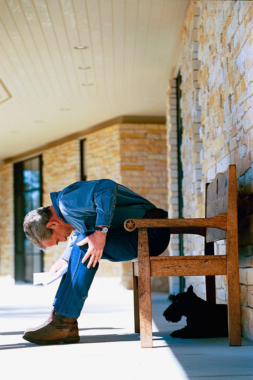 President George W. Bush glances down at Barney as he sits on the porch Saturday, March 6, 2004, at Prairie Chapel Ranch in Crawford, Texas.  Photographs by Eric Draper from Front Row Seat: A Photographic Portrait of the Presidency of George W. Bush(Copyright © 2013). For more information visit www.utexaspress.com