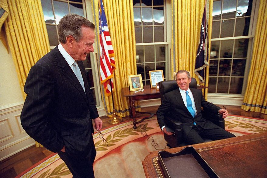 As his father, former President George H.W. Bush, looks on, President George W. Bush sits at the Resolute Desk Jan. 20, 2001, in the Oval Office for the first time.  Photographs by Eric Draper from Front Row Seat: A Photographic Portrait of the Presidency of George W. Bush(Copyright © 2013). For more information visit www.utexaspress.com
