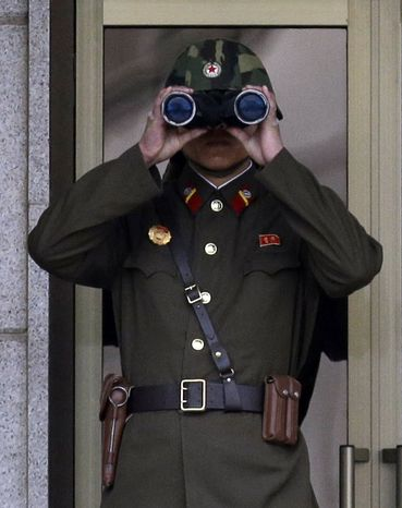 A North Korean soldier looks toward South Korea through a pair of binoculars at the border village of Panmunjom in the Demilitarized Zone, which has separated the two Koreas since the Korean War, on Tuesday, April 23, 2013. (AP Photo/Lee Jin-man)