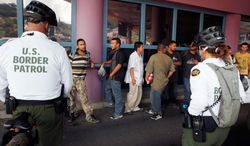** FILE ** This file photo taken July 28, 2010, shows a group of illegal immigrants waiting in line while being deported to Mexico at the Nogales Port of Entry in Nogales, Ariz. (AP Photo/Jae C. Hong, File)