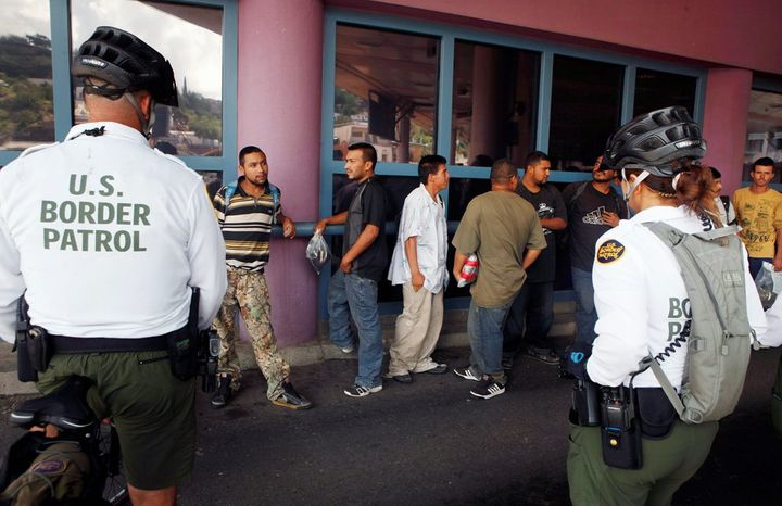 ** FILE ** This file photo taken July 28, 2010, shows a group of illegal immigrants waiting in line while being deported to Mexico at the Nogales Port of Entry in Nogales, Ariz. (AP Photo/J