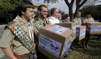 **FILE** James Oliver (left) hugs his brother and fellow Eagle Scout, Will Oliver, who is gay, as Will and other supporters carry four boxes filled with a petition to end the ban on gay scouts and leaders in front of the Boy Scouts of America headquarters in Dallas on Feb. 4, 2013. (Associated Press)