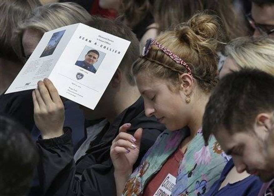 Mourners bow their heads during a memorial service for fallen Massachusetts Institute of Technology campus officer Sean Collier at MIT in Cambridge, Mass. Wednesday, April 24, 2013. Collier was fatally shot on the MIT campus Thursday, April 18, 2013. (AP Photo/Elise Amendola)