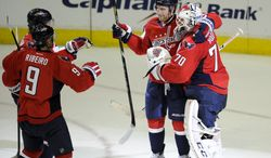 Washington Capitals goalie Braden Holtby (70) celebrates their 5-3 win over Winnipeg Jets with Karl Alzner, second from right, and Mike Ribeiro (9) after an NHL hockey game, Tuesday, April 23, 2013, in Washington. (AP Photo/Nick Wass)