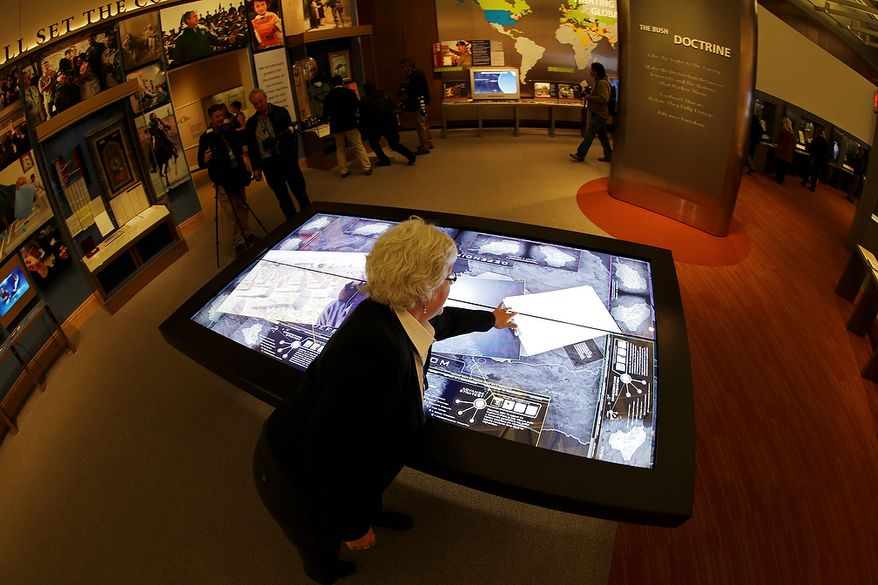 Docent Patricia Flynn demonstrates an interactive with information about conflicts in Afghanistan and Iraq during a tour of the George W. Bush Presidential Center Wednesday, April 24, 2013, in Dallas. More than 8,000 people are expected to attend the invitation-only dedication of the center, Thursday, April 25, which will house the presidential library and museum along with the 43rd presidentís policy institute. It opens to the public on May 1.  (AP Photo/David J. Phillip)