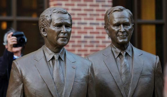 Statues of former Presidents George W. Bush, left and George HW Bush are seen during a tour of the George W. Bush Presidential Center Wednesday, April 24, 2013, in Dallas. (AP Photo/David J. Phillip)