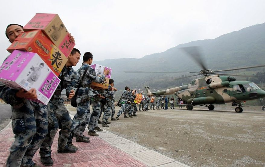 Chinese soldiers unload relief supplies from a helicopter in quake-ravaged Sichuan province. Saturday's 7.0-magnitude earthquake killed at least 186 and injured thousands. The military is in full control of relief and rescue, with citizen-initiated efforts to help strictly banned.