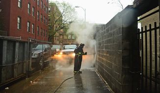 Sanitation worker Sean Thomas uses hot water to remove graffiti from walls in the District on Thursday. Mr. Thomas has been cleaning graffiti for 10 years.(Andrew Harnik/The Washington Times)