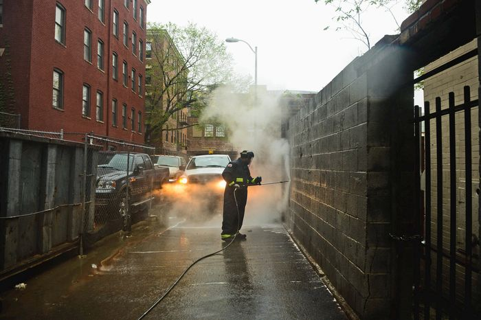 Sanitation worker Sean Thomas uses hot water to remove graffiti from walls in the District on Thursday. Mr. Thomas has been cleaning graff