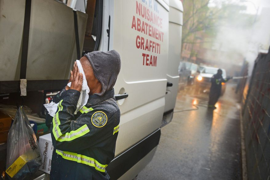 Sanitation Worker Denita Taylor [cq], left, with the District's Nuisance Abatement Graffiti Team wipes water from her face as she and Sean Thomas, right, power washes graffiti with hot water to remove it from walls in an alley near 14th and U Streets, Northwest, Washington, D.C., Thursday, April 18, 2013. (Andrew Harnik/The Washington Times)