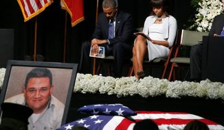 President Obama and first lady Michelle Obama bow their heads behind a photo of volunteer firefighter Capt. Cyrus Adam Reed, who was killed, at Thursday's memorial service for victims of last week's fertilizer plant explosion in West, Texas.